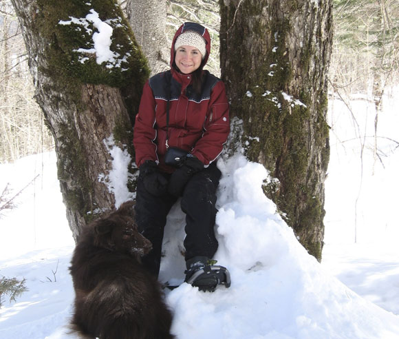 Photo of Édith Bégin in winter, between two trees, and with a long brown-haired dog at her feet